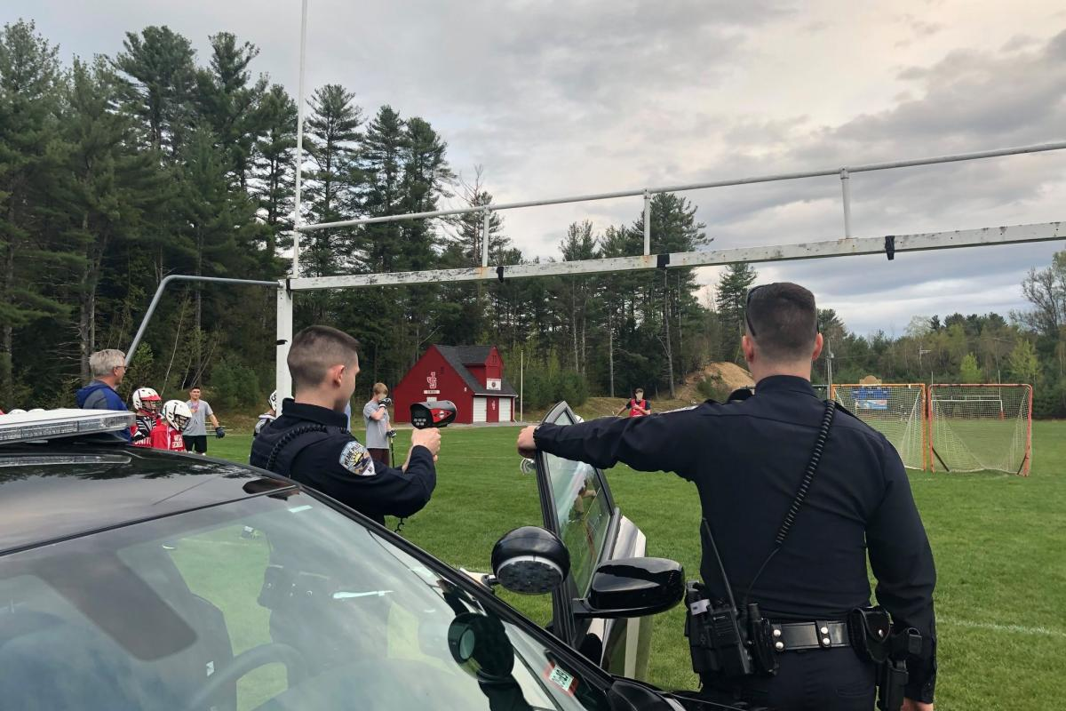 Officer Lewis and Officer Belletete assisting the lacrosse team track the speeds of their passes